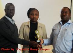 Evelyn Wambui receives a transformational award from Capacity Kenya's, Mathew Thuku and CHAK's Patrick Kyalo