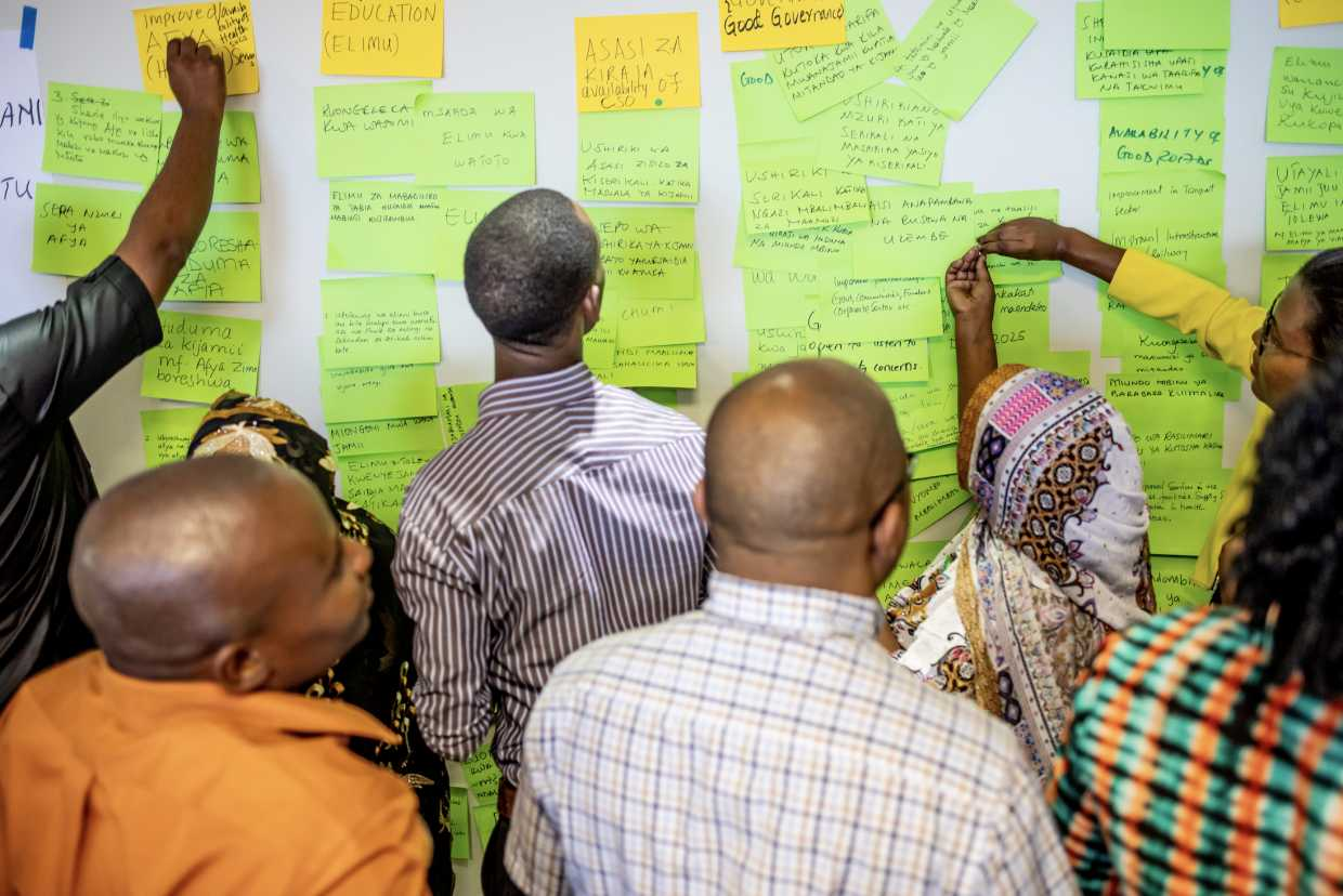Pact staff and community members in Tanzania take part in a workshop before the Covid-19 pandemic to gather ideas for improving Pact's programming