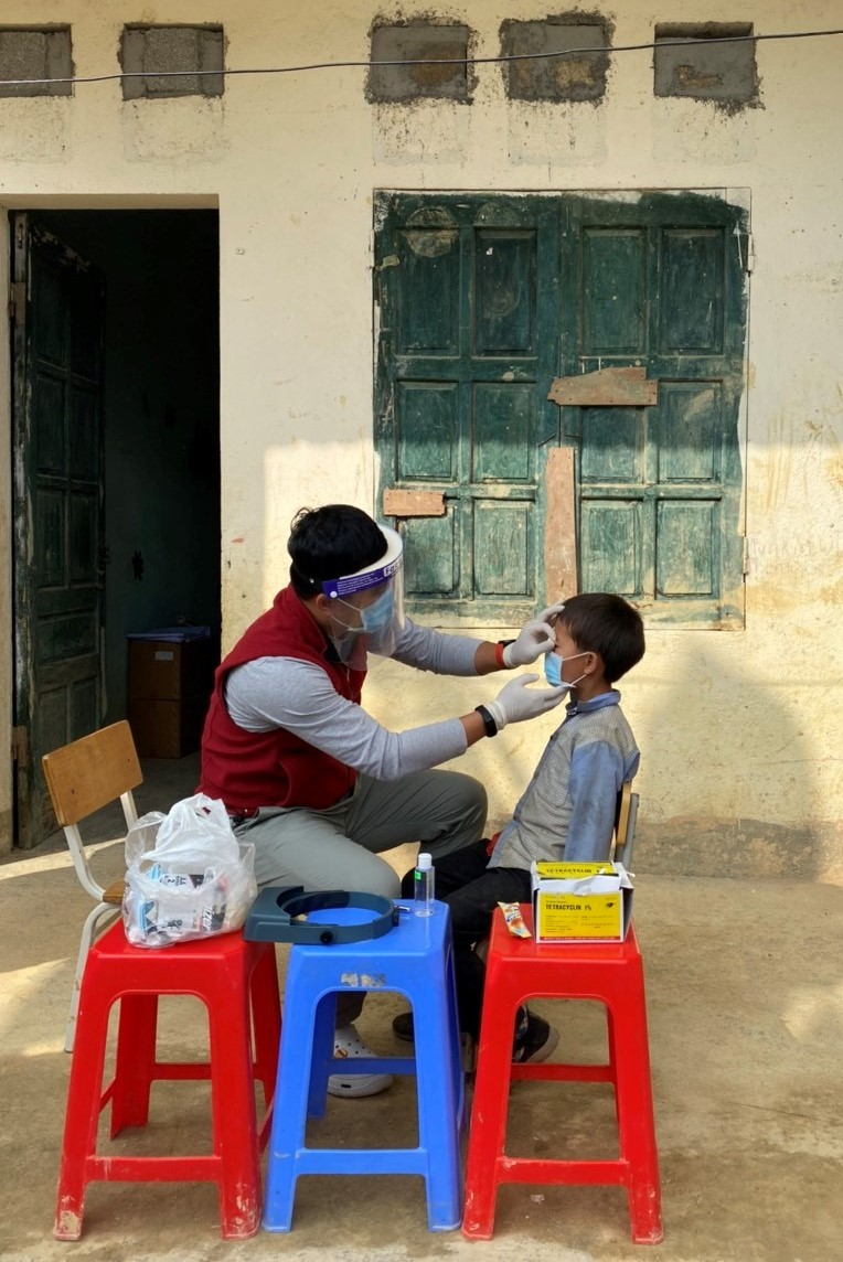 During routine survey in Viet Nam, a trachoma grader in examines the eyelid of a child for signs of trachoma. Grader wears a face shield, mask, and gloves as additional safety precautions during the COVID-19 pandemic