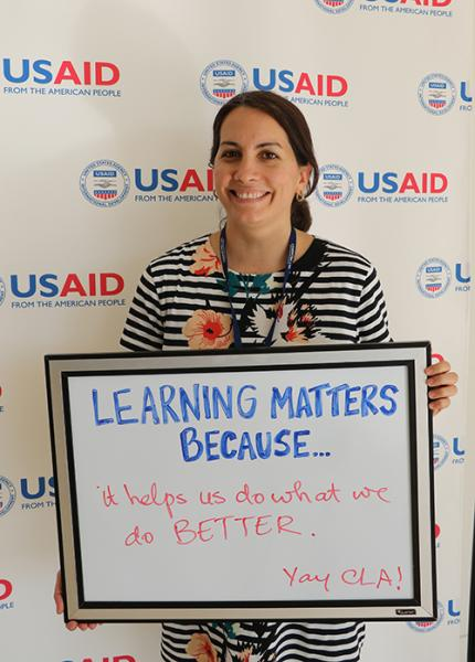Image of Christine holding Learning Matters sign