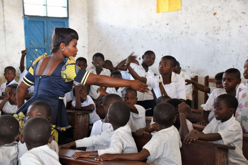 Photo of teacher and students in DRC